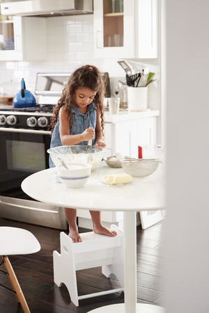 Young girl making a cake in the kitchen on her own, mixing cake mix with a whisk, vertical Reklamní fotografie