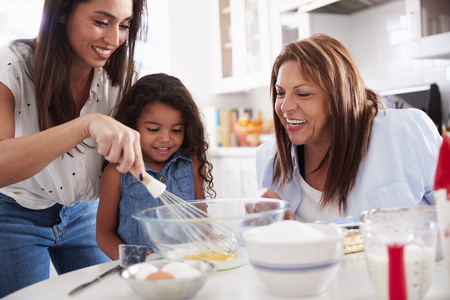 Young girl making a cake in the kitchen with her mum and grandmother, close up