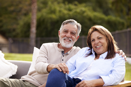Senior couple sitting together on a seat in the garden smiling to camera, front view