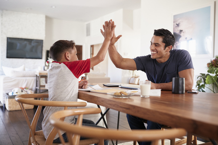 Hispanic father and son sitting opposite each other, high five over the dining room table, side view