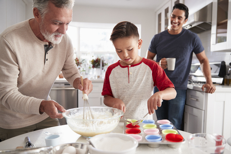 Dad watching his son making cakes with grandad at the kitchen table, close up Standard-Bild - 115389145