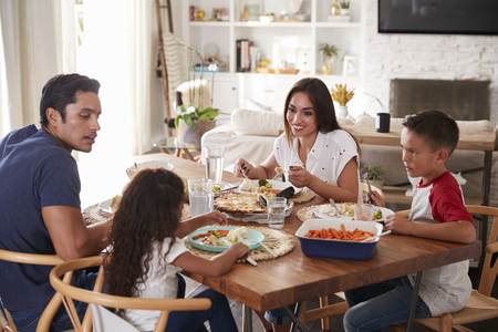 Young Hispanic family sitting at dining table eating dinner together