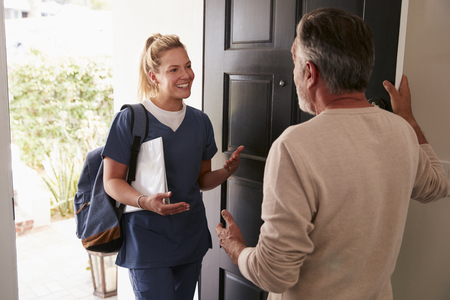 Senior man opening his front door to a female healthcare worker making a home health visit