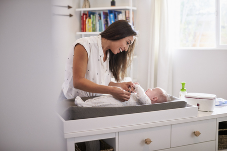 Happy mother changing the diaper of her newborn son at home on changing table, selective focus