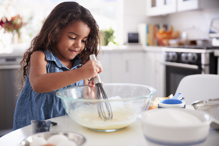 Young Hispanic girl making a cake in the kitchen on her own, close up 版權商用圖片