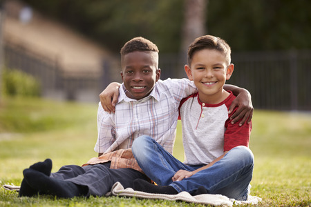Two pre-teen male friends sitting on the grass in a park, arms around each other, looking to camera Stock Photo
