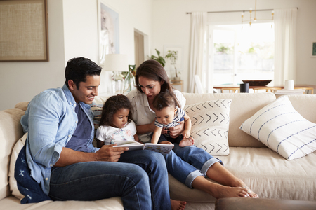 Hispanic couple sitting on the sofa reading a book at home with their baby son and young daughter Stockfoto