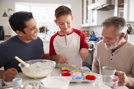 Three male generations of family making cakes together at the table in the kitchen, close up Stock Photo