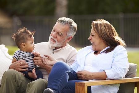 Senior paar zitten in de tuin met hun kleinzoon, glimlachend naar hem, vooraanzicht