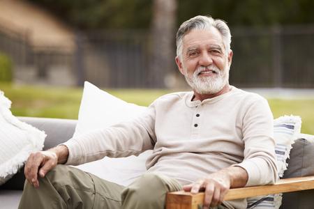 Happy senior Hispanic man sitting on a seat in the garden smiling to camera, close up Reklamní fotografie