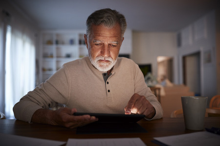 Senior Hispanic man sitting at a table reading an e book at home in the evening, close up Imagens