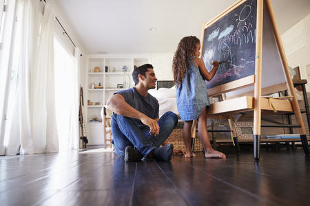 Hispanic dad sitting on the floor in sitting room watching his young daughter drawing on blackboard