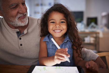Senior Hispanic man with his young granddaughter using stylus and tablet computer, smiling to camera