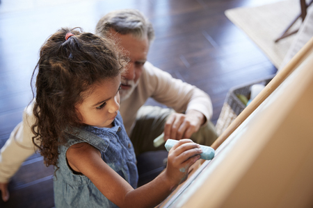 Senior man sitting on the floor watching his granddaughter drawing on a blackboard, elevated view