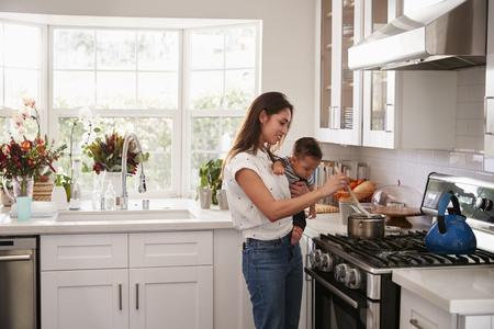 Maman multitâche tenant son jeune bébé pendant qu'elle prépare de la nourriture sur la plaque de cuisson dans sa cuisine, vue latérale