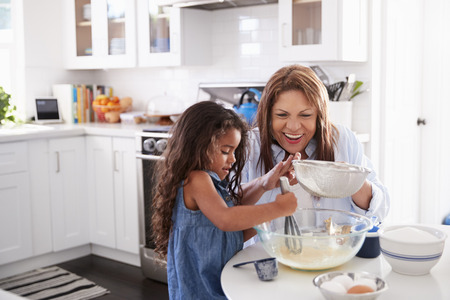 Young Hispanic girl making cake in the kitchen with her grandma, looking down Imagens