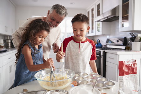 Brother and sister standing at the kitchen table mixing cake mix with their grandfather, close up Stock Photo
