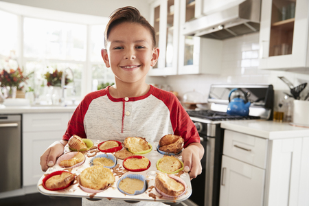 Proud pre-teen Hispanic boy standing in kitchen presenting the cakes heÕs made to camera, close up