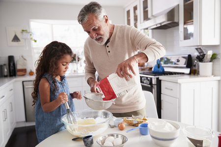 Young girl preparing cake mixture with her grandfather at the kitchen table, close up Stock fotó - 115390747