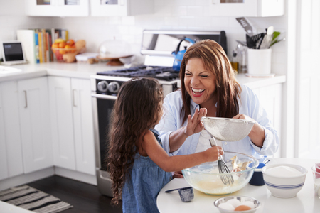 Young Hispanic girl making cake in the kitchen with her grandma, looking at each other Banque d'images