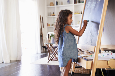 Young Hispanic girl drawing with chalks at a blackboard in the living room at home, side view Stock Photo