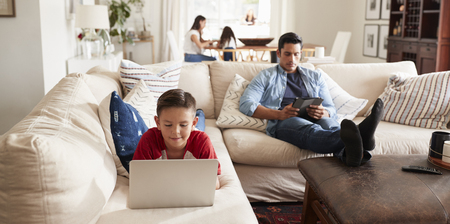 Pre-teen boy lying on sofa using laptop, dad sitting with tablet, mum and sister in the background 免版税图像