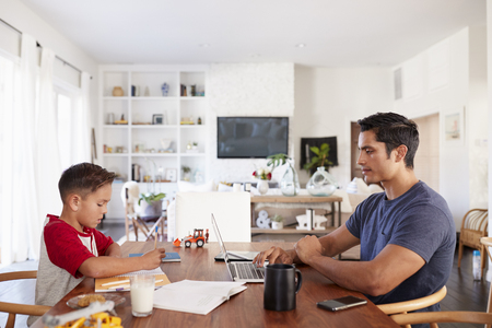 Hispanic father and son working opposite each other at the dining room table, side view, close up