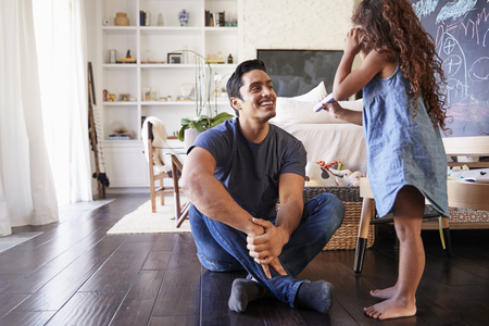 Hispanic dad sitting on the floor in sitting room listening his young daughter, side view