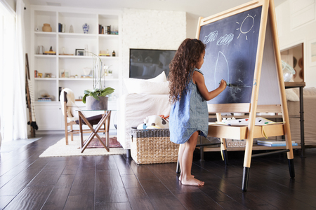 Young Hispanic girl drawing with chalks at a blackboard in the living room at home, full length