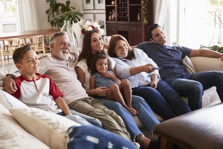 Three generation Hispanic family sitting on the sofa watching TV, grandmother using remote control