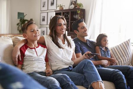 Giovane famiglia ispanica seduta sul divano di casa a guardare la TV insieme, da vicino