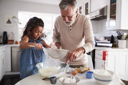 Young girl preparing cake mixture with her grandfather at the kitchen table, close up