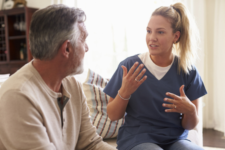 Female healthcare worker sitting with a senior Hispanic man in his living room during a home visit
