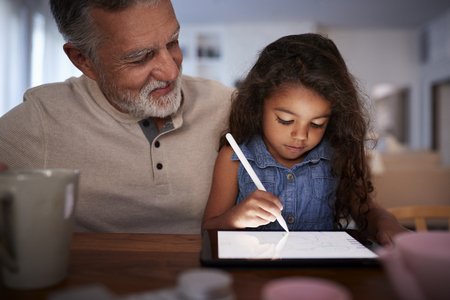 Senior Hispanic man with his young granddaughter using stylus and tablet computer, front, close up
