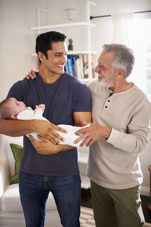 Proud senior Hispanic man standing with his adult son holding his four month old boy, vertical