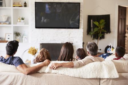 Vista posterior de la familia hispana de tres generaciones sentados en el sofá viendo la televisión Foto de archivo