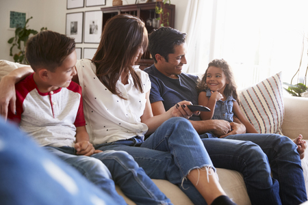 Young Hispanic family sitting on the sofa at home to watch TV, looking at each other, close up