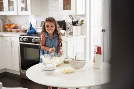 Young girl in the kitchen making cake mixture on her own, looking to camera