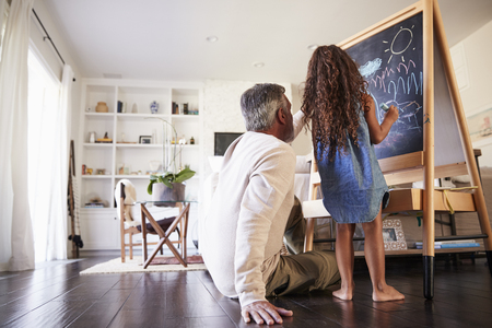 Grandfather sitting on the floor drawing on a blackboard with his young granddaughter, low angle 写真素材 - 115390878