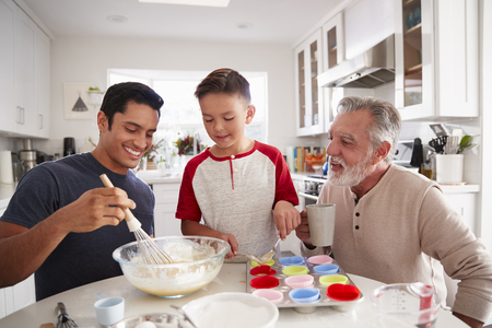 Three male generations of family preparing cakes together at the table in the kitchen, close up