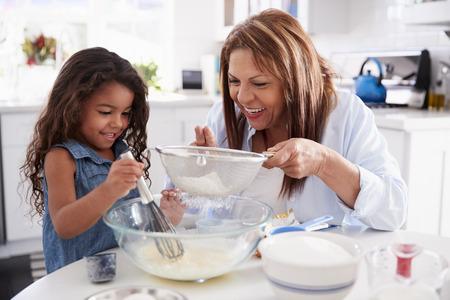 Junges hispanisches Mädchen, das mit ihrer Oma Kuchen in der Küche macht, Nahaufnahme Standard-Bild