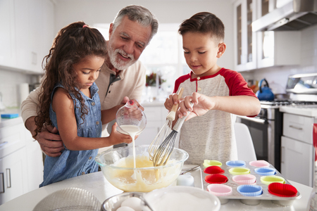 Brother and sister standing at the kitchen table making cake mix with their grandfather, close up 写真素材