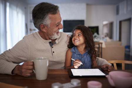 Senior Hispanic man with his granddaughter using tablet computer, looking at each other, front view