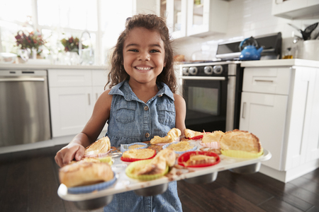 Young Hispanic girl standing in kitchen presenting cakes sheÕs baked and smiling to camera Banco de Imagens