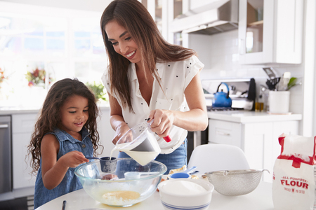 Young Hispanic girl making cake in the kitchen with help from her mum, waist up 版權商用圖片