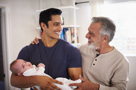 Proud senior Hispanic man standing with his adult son holding his four month old boy 版權商用圖片 - 115391015