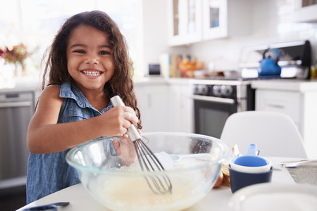 Young Hispanic girl making cake mix in the kitchen on her own, smiling, close up