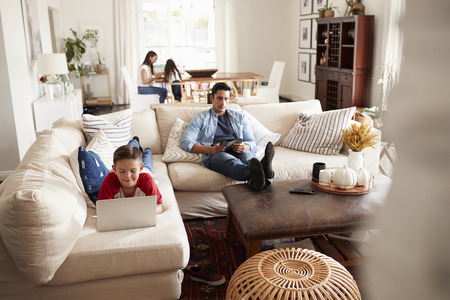 Pre-teen boy lying on sofa using laptop, dad sitting with a tablet, mum and sister in the background