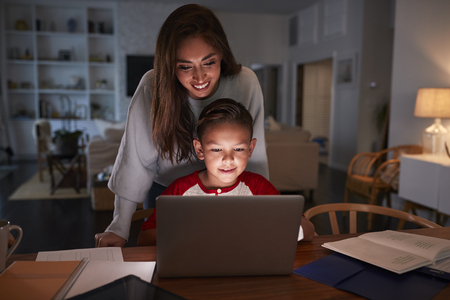Hispanic woman looking over her son�s shoulder while he does his homework using laptop computer