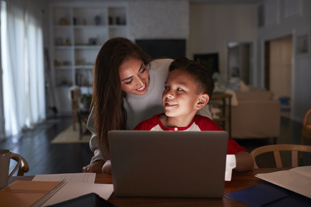 Hispanic woman looking over her sonÕs shoulder while he does his homework using laptop computer